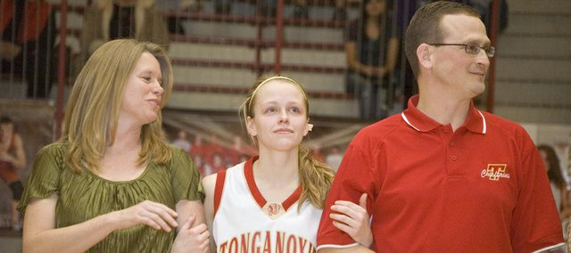 Tonganoxie High senior guard Lauren Hall, flanked by mother Carla and father David (a THS assistant coach), looks up into the home crowd during a Senior Night ceremony following the Chieftains' 52-41 home loss to Piper.