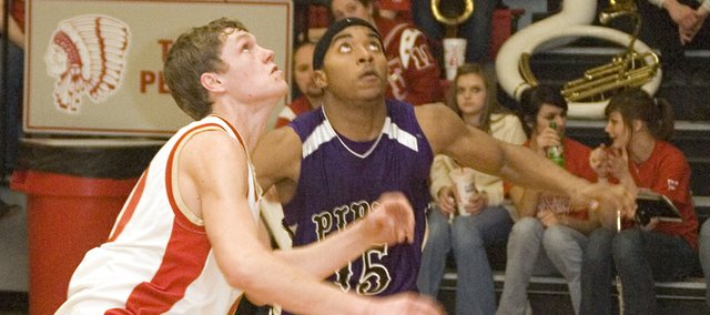 Tonganoxie High senior forward Justin Jacobs and Piper senior guard Jasper Sanders get low as they prepare to go after a rebound on Friday night. The Chieftains defeated the Pirates, 68-62, on Senior Night.