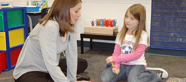 Eudora West Early Childhood and Family Center kindergarten instructor Mandy Meyer helps kindergartner Rylee Calhoon with a language arts activity.