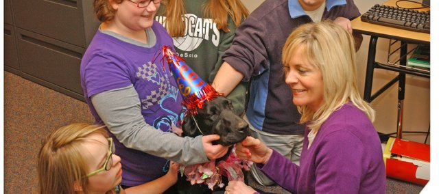 Lexington Trails Middle School counselor Angie Russell, lower right and students treat Abby, the school's service dog, to a party for her fourth birthday Monday. The dog owned by Russell's neighbors comes to the school daily to work with students.