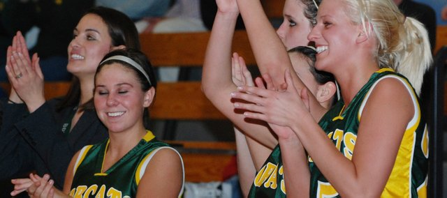 Basehor-Linwood players Taylor Johnson (3), Courtney Poe (11) and Cassy Bever (25) celebrate as the final seconds tick off the clock in their 53-37 victory against St. James Academy in the Class 4A substate semifinals.