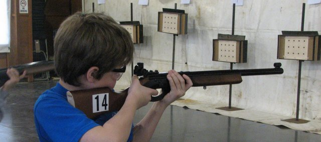 David Porter, 9, of De Soto, aims and fires during the BB gun competition Saturday at Camp Naish. The two-day shooting sports competition drew more than 160 4-Hers from throughout the state of Kansas.