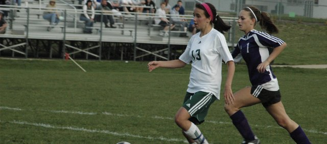 Carly Stanley (13) pushes the ball up the field during a game last season. Stanley, senior, will move to the middle and should continue to provide the girls soccer team with scoring ability. The Wildcats open the season against Spring Hill March 25 at De Soto.