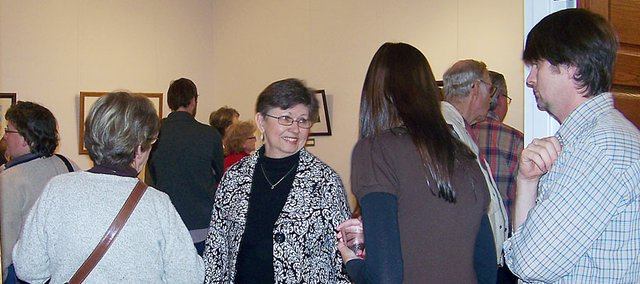 Local artist Rosemary Murphy, center, greets some of the 200 people who came Sunday for the opening exhibit at the Lumberyard Arts Center.