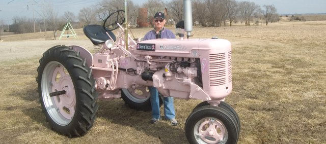 Harold Denholm stands with Mom's Tractor, which he and his son, Greg, restored pink to honor Haorld's wife, Aileen, who died from breast cancer in 2007. The Denholms plan to enter the tractor in this year's Tonganoxie St. Patrick's Day Parade.