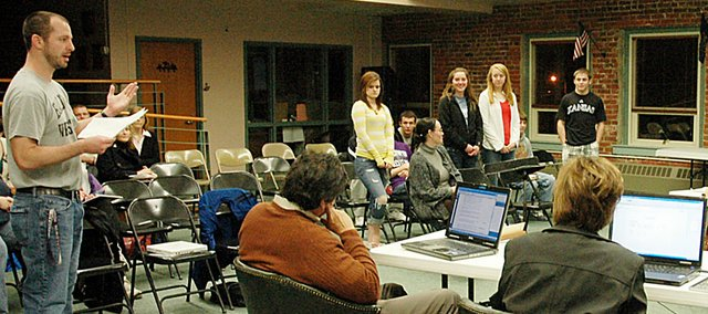 The Baldwin School Board listens Monday night as Kit Harris, left, introduces journalism students who were recognized for their achievements. He did the same with his wrestling team that finished ninth at the recent Class 4A State Tournament in Salina.