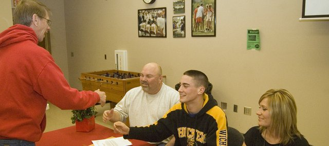 DJ Lindsay, center, extends his hand to Tonganoxie High girls track coach Chris Weller, who was congratulating the Chieftains senior sprinter for signing with Wichita State University on March 11. Lindsay's parents, Dennis and Kim, joined him in the Chieftain Room for the signing ceremony.
