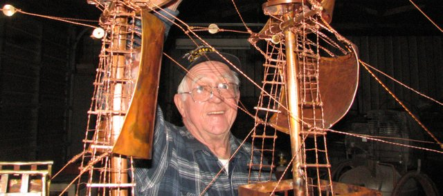 Harold Leible points to the copper ropes he made for his Mayflower ship. Leible constructed the entire 300-pound ship out of junk metal.