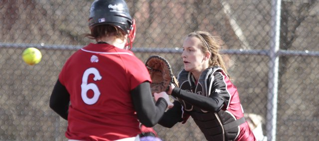 Lawrence High catcher Kristen Bell awaits a throw to home to force out Shawnee Mission North runner Cally Cowan during the fifth inning of the Lions' first game, Thursday, March 25, at Lawrence High School.