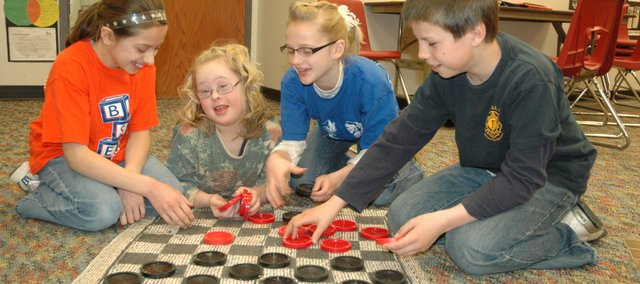 General education fifth-graders at Bonner Springs Elementary play a game of checkers with special education student Paige Hammon, second from left. The fifth-graders have taken it upon themselves to befriend and help out their special education classmates. Pictured are, from left, Karli Trumbo, Paige, Alayna Dooley and Preston Landers.