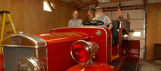 Suzy and Larry Ross sit in a 1936 vintage pumper truck to be on display in the Tonganoxie Community Historical Society's new fire station Saturday as part of the organization's open house. The event, which will mark the start of the museum's season, will be from 10 a.m. to 5 p.m. Saturday at the museum, 201 W. Washington Street. The Bald Eagle Re-enactors will provide a glimpse into the life of 1840-era mountain men at the event.