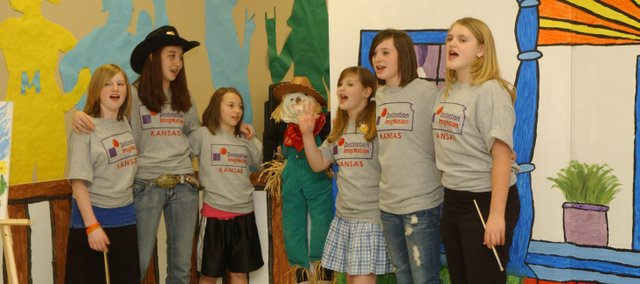 A team of Tonganoxie Middle School sixth-graders, Shannon Olson, Haley Arevalo, Nicole Zerrer, Emma DeMaranville, Emily Ebert and Emily Jardes, end with a song the skit they preformed at the state Destination ImagiNation competition Saturday at Tonganoxie Middle School. Team member Shannon Haufler manipulated the scarecrow puppet.