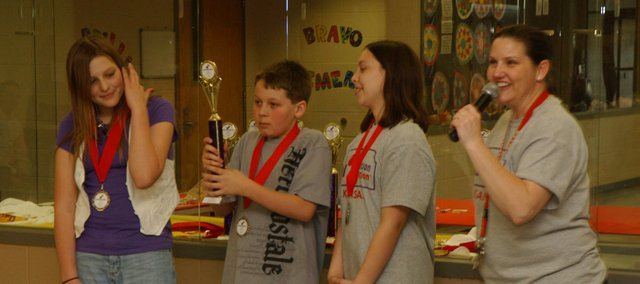 A Clark Middle School team of (from left) Mikaela Bennett, Tyler Campbell and Madison Stumbough, show off a first-place trophy and medals awarded to them by Tonganoxie Middle School Principal Jill Dickerson at the state Destination ImagiNation competition in Saturday in Tonganoxie. The students entered a robot competition.