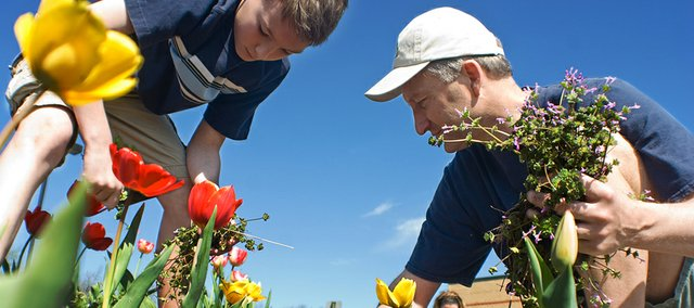 Doug Pickert, right, and his son Ben Pickert, help pull weeds from the school's flower bed.