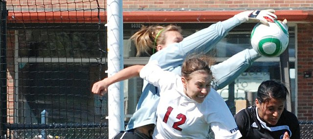 St. James Academy's Sarah Grant battles the Grandview goalkeeper for the ball after a St. James freekick. Grandview scored a late goal and won the game, 1-0.