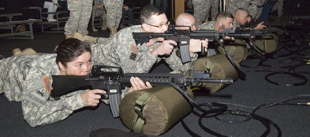 Army personnel take aim at the new simulated firing program installed in a new building at Fort Leavenworth. A ribbon-cutting took place Friday. Pictured far left are 1st Sgt. Sharron Altamirano and Col. Wayne Green.
