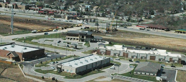 Construction of an interchange at Johnson Drive and Kansas Highway 7 is at the front door for the Woodsonia West shopping center (foreground). Johnson Drive access has been closed to K-7 motorists, who must go north to 47th Street and then return south to Johnson Drive via Silverheel Road and Woodsonia Drive. The city and state have taken steps to help businesses in the area, including allowing increased promotional signage.