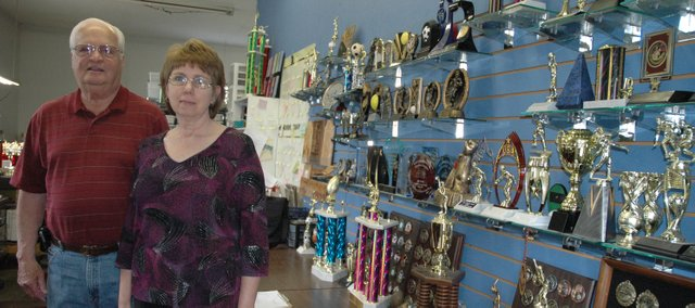 Wes Mills and wife, Beverly, stand next to a wall in their shop of available trophies, medals and plaques. The two have run Mills Trophies and More, a trophy and engraving business, out of their home at 634 N. Nettleton since 2004.