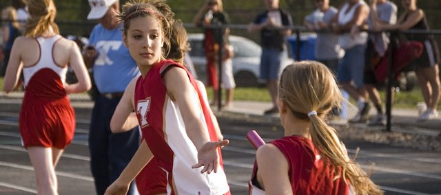 Tonganoxie High freshman Abby Thomas reaches out for the baton as 4x800 relay teammate Lauren Hall approaches. The THS girls won that event and eight others on their way to capturing the team title at the Tonganoxie Invitational on Thursday.