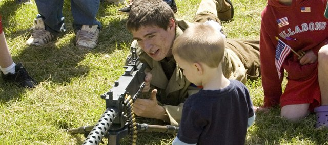 World War II re-enactor Mason McClure demonstrates how a World War II machine gun is operated Saturday after the McLouth Patriots Day Parade. Getting an up-close look is Lawrence McCawley, 3, Lawrence.