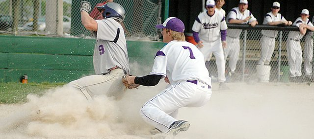 Baldwin High School junior Josh Hoffman slides past the Louisburg pitcher to score Baldwin's only run of the Bulldogs' first game Tuesday.