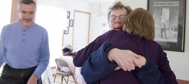 Sara Schmanke, back, hugs Gwen Wiens, leader of a Lawrence Huntington's disease support group, during a visit to the Schmanke's home Wednesday, April 28, 2010, in Baldwin City. At left is Sara's husband, Dean Schmanke.