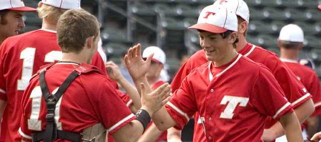 Tonganoxie High pitcher Dylan Puhr is congratulated by catcher Jeremy Wagner after throwing a complete game to earn an 8-3 victory against Paola on Saturday at the Butch Foster Memorial Baseball Classic in Kansas City, Kan.