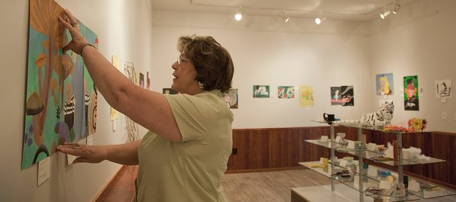 Diane Niehoff, co-founder of the Lumberyard Arts Center, Baldwin City, hangs a piece of children's artwork in the gallery. The site opened earlier this spring with a gallery, classrooms and kitchen. A theater under construction is part of phase two.
