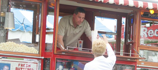 Red Truck Novelties, of Shawnee, serves up hot buttered popcorn to 2010 Kansas Sampler Festival attendees through the windows of a 1929 Ford Model AA popcorn truck.