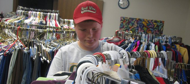 Basehor-Linwood Middle School eighth-grader Avery Fliger organizes racks of clothes at the community clothes closet he organized at Holy Angels Catholic Church. The closet provides families in need with free clothes.