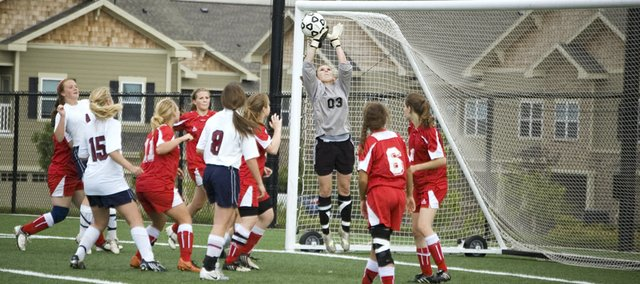 Tonganoxie High goalkeeper Alex Bartels elevates to knock away a St. James Academy shot attempt in the first half of a regional playoff match at Overland Park Soccer Complex. The Chieftains' season came to a close with an 8-0 loss.
