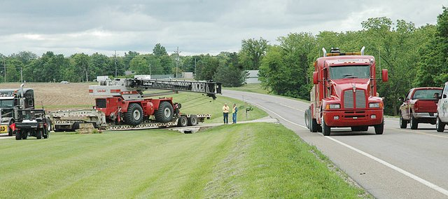 U.S. Highway 56 east of Baldwin City is back open after a stranded semi-tractor trailer was finally able to maneuver out of Bob Rohe's driveway where it had become stranded Thursday night. Rohe is in the middle of the picture talking with a trucking company employee. The highway was closed on and off for about an hour and a half.