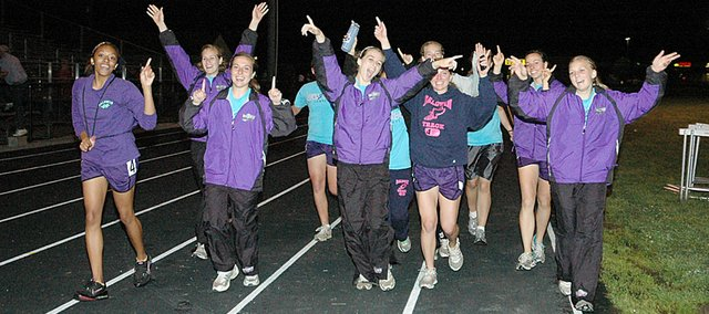 Members of the Baldwin High School girls' track and field team celebrate their Class 4A regional championship with a victory lap Friday night after the meet.