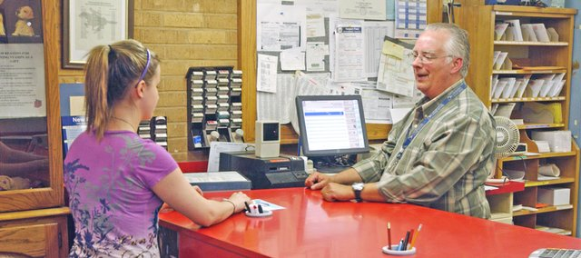 Kayla Leffert requests a change-of-address Tuesday from Tonganoxie Postmaster Ron Hubbard. From 600 to 900 customers a day visit the post office, adding traffic to downtown that will disappear when the post office moves to its new site in northeast Tonganoxie in the coming weeks.