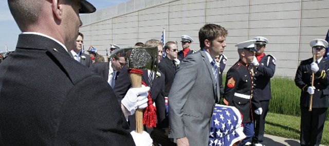 Pallbearers carry Firefighter John Glaser's casket into United Methodist Church of the Resurrection for his funeral.