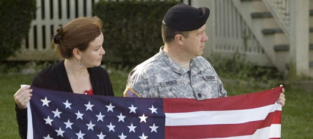 People in attendance for Thursday's processional hold a flag along Grant Avenue at Fort Leavenworth.