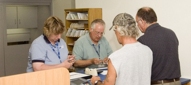 Post Office officials assist customers Monday morning at the new Tonganoxie Post Office. The office opened at its new location north of U.S. Highway 24-40 after several years of existing in downtown Tonganoxie.