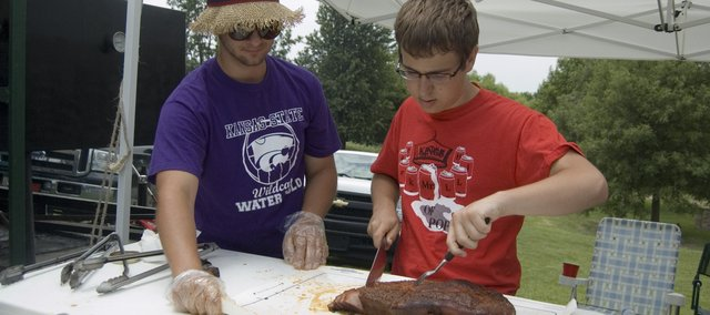 Ben Shinogle, right, slices brisket as his brother, Charlie, assists him. Ben, who is 15, competed in Saturday's McLouth BBQ Blowout. The event was at Prairie Park in McLouth.