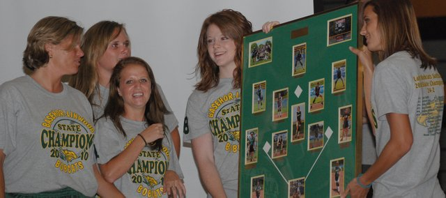 Basehor-Linwood's softball seniors present a photo collage to coach Susan Mayberry on Monday at the pep assembly for the state championship softball team.