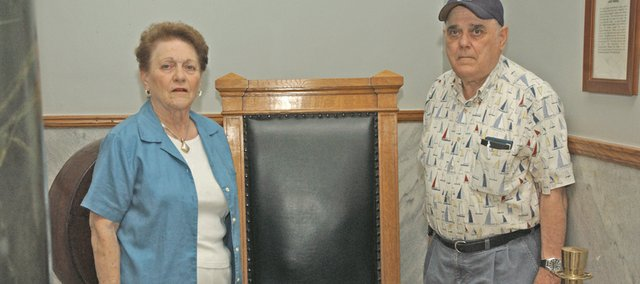 A chair their father and other Leavenworth County District Court judges sat in while dispensing justice separates siblings Jean Will and Ben Dawes. The family returned the chair to the Leavenworth County Courthouse, where it is part of the second-floor display.