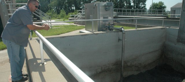 """Ron Wyatt, chief wastewater plant operator, surveys the liquid wastewater, or """"sludge,"""" as it is aerated during the sludge conditioning process. In addition to the new sludge conditioning equipment, the Wastewater Treatment Plant has been outfitted with a new belt filter press and building to house the belt filter in."""