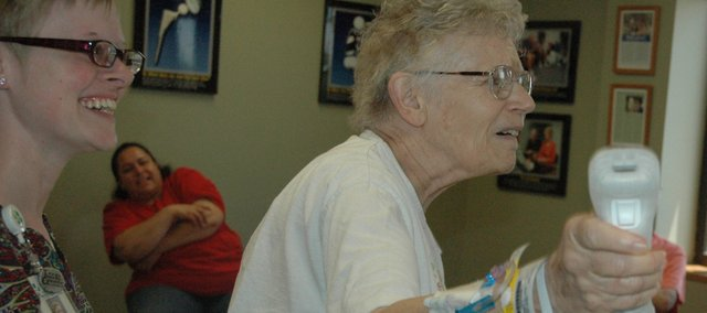 Nancy Watkins, at right, tries her hand for the first time at the Nintendo Wii, which was part of her physical therapy process at Providence Medical Center following a joint replacement surgery. The Wii is being used to aid in the recovery process by promoting movement and balance. At left is occupational therapist Kate Felchlia.