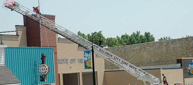 Baldwin City Volunteer Firemen were sprucing the fire station up Friday by painting the flag pole. An open house celebrating the department's 100 years of serving Baldwin City will be from 1 p.m. to 5 p.m. Sunday at the fire station.