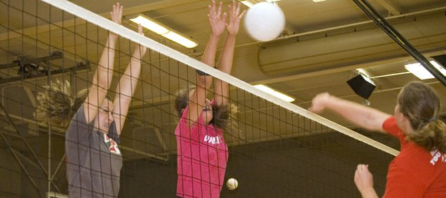Hannah Kemp and Molly O'Hagan extend their arms to attempt a block at the net on Thursday at Chieftains volleyball camp.