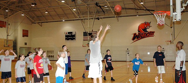 Kansas University star freshman Josh Selby, right, watches his team compete in a shooting competition Friday morning at the Baker University basketball camp. Selby and KU senior Tyrel Reed came down from Lawrence to help first-year Baker University coach Brett Ballard, who is the former director of basketball operations at KU. The KUplayers were a hit with the campers.
