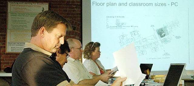 Baldwin School Board Member Scott Lauridsen reviews the printed version of the slide show that was presented at June's meeting about the state of the district's buildings.
