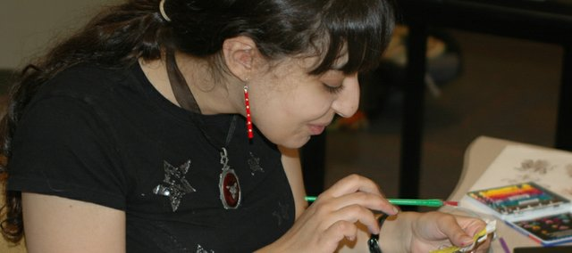Ayah Abdul-Rauf works on a collage journal at Johnson County Central Resource Library. Ayah is this year's Teen Writer-in-Residence.