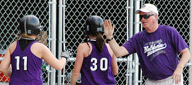 Baldwin High School coach Bob Martin high-faves sophomore Madeline Brungardt (No. 30) and junior Morgan Burton during a game this spring. On Monday, Martin's resignation as the BHS softball coach was approved.