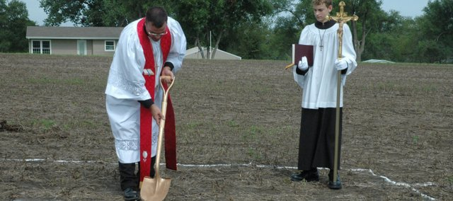 The Rev. Robert Weinkauf breaks ground Sunday at the new site of Risen Savior Lutheran Church in Basehor. Kaleb Weinkauf, right, acted as the crossbearer for the ceremony.