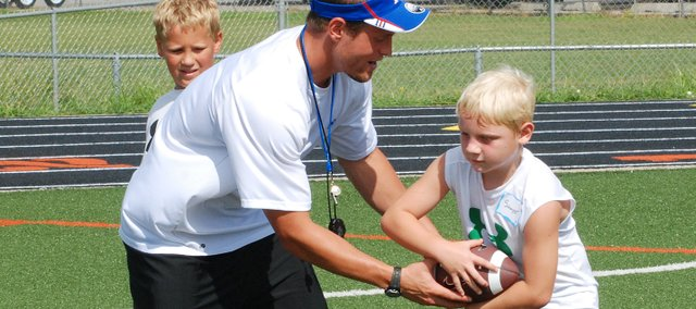 Former Kansas University running back Jake Sharp hands off the ball to a camper during a running back drill on Saturday at Sharp's clinic at David Jaynes Stadium in Bonner Springs. The camp was conducted in affiliation with the Bonner Springs Family YMCA.